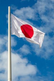 Vlag van japan fladdert op een vlaggenmast tegen de hemel met wolken