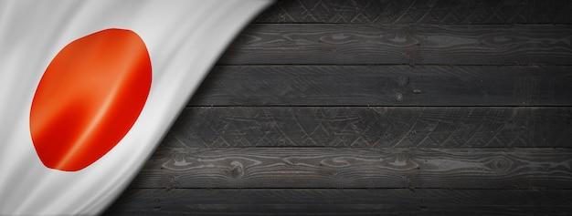 Vlag van japan op zwarte houten muur. horizontale panoramische banner.