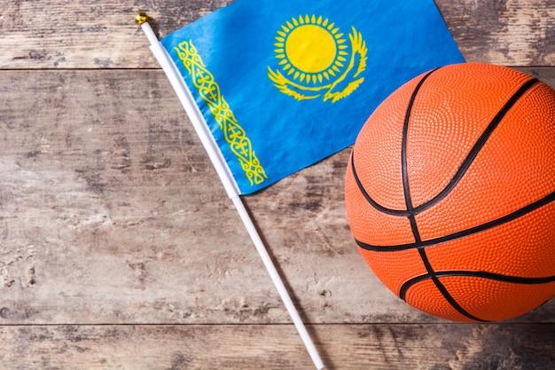 Vlag van kazachs en basketbal op houten tafel met kopie ruimte