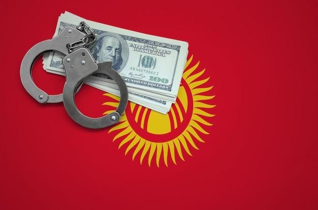 Vlag van kirgizië met handboeien en een bundel dollars. het concept van het overtreden van de wet en dieven misdaden