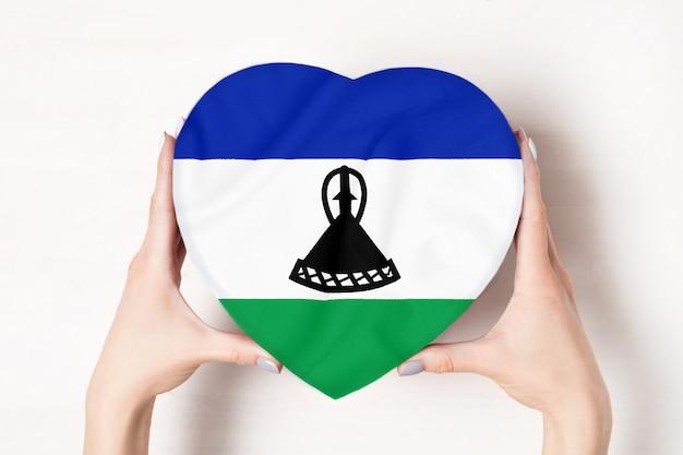 Vlag van lesotho op een hartvormige doos in een vrouwelijke handen.
