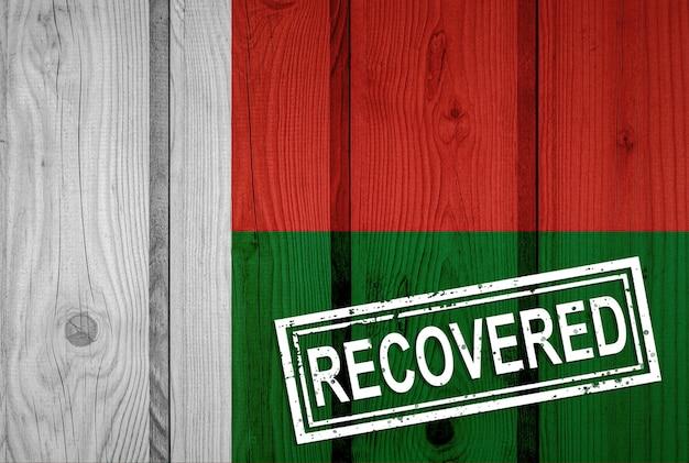 Vlag van madagaskar die de infecties van de corona-virusepidemie of coronavirus heeft overleefd of hersteld. grunge vlag met stempel hersteld