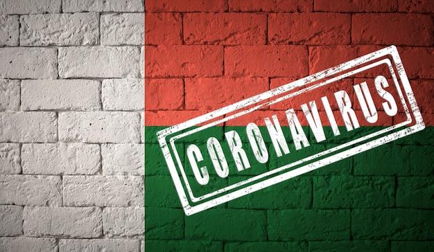 Vlag van madagaskar op bakstenen muurtextuur. gestempeld met het coronavirus. corona-virusconcept. op de rand van een covid-19- of 2019-ncov-pandemie. nieuwe uitbraak van het chinese coronavirus