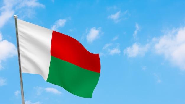 Vlag van madagaskar op paal. blauwe lucht. nationale vlag van madagaskar