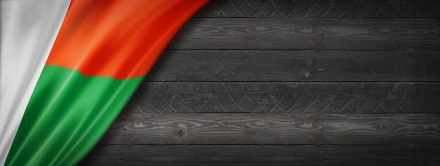 Vlag van madagaskar op zwarte houten muur. horizontale panoramische banner.