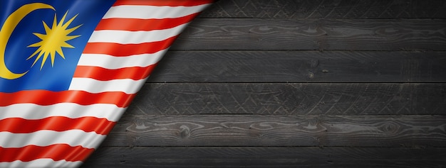 Vlag van maleisië op zwarte houten muur. horizontale panoramische banner.