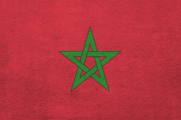 Vlag van marokko afgebeeld in heldere kleuren op oude reliëf pleisterwand.