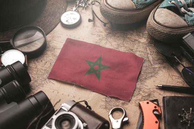 Vlag van marokko tussen de accessoires van de reiziger op oude vintage kaart. toeristische bestemming concept.