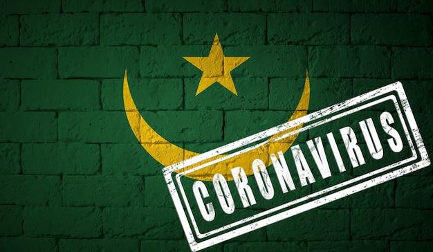 Vlag van mauritanië op bakstenen muur textuur. gestempeld met het coronavirus. corona-virusconcept. op de rand van een covid-19- of 2019-ncov-pandemie. nieuwe uitbraak van het chinese coronavirus