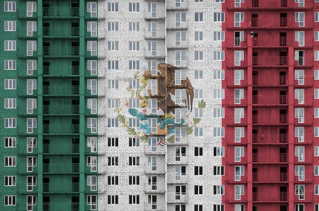 Vlag van mexico afgebeeld in verfkleuren op residentiële gebouw met meerdere verdiepingen in aanbouw.