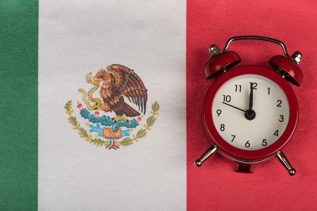 Vlag van mexico en vintage wekker. tijd om naar mexico te reizen