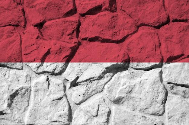 Vlag van monaco afgebeeld in verfkleuren op oude stenen muur close-up.