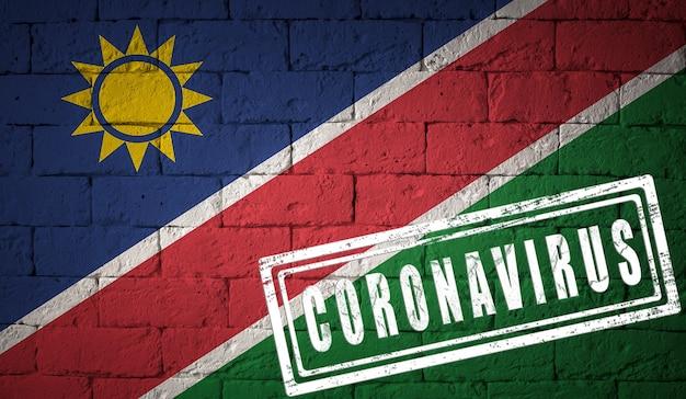Vlag van namibië op bakstenen muurtextuur. gestempeld met het coronavirus. corona-virusconcept. op de rand van een covid-19- of 2019-ncov-pandemie. nieuwe uitbraak van het chinese coronavirus