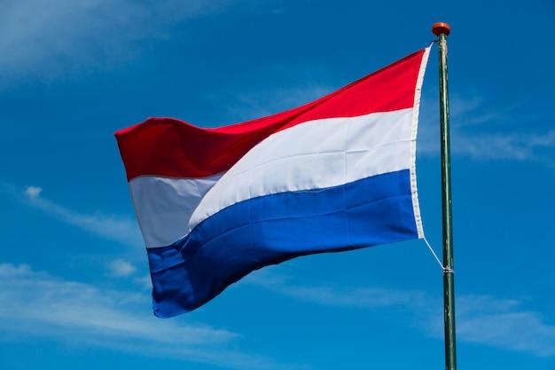 Vlag van nederland die in de wind tegen blauwe hemel golven