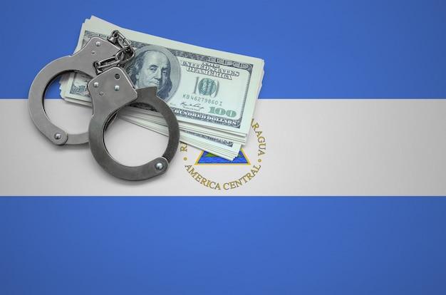 Vlag van nicaragua met handboeien en een bundel dollars. het concept van het overtreden van de wet en dieven misdaden