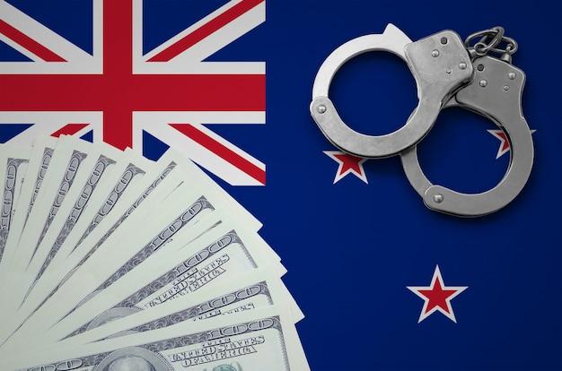 Vlag van nieuw-zeeland met handboeien en een bundel dollars. het concept van illegale bankactiviteiten in amerikaanse valuta