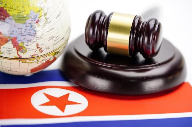 Vlag van noord-korea en rechter hamer met globe wereldkaart. wet en gerechtshof concept.