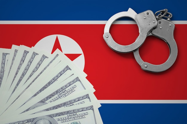 Vlag van noord-korea met handboeien en een bundel dollars. het concept van illegale bankactiviteiten in amerikaanse valuta