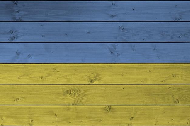 Vlag van oekraïne afgebeeld in heldere verfkleuren op oude houten muur. getextureerde banner op ruwe achtergrond