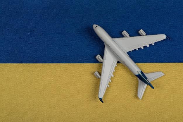 Vlag van oekraïne en modelvliegtuig. hervatting van vluchten na quarantaine, openen grenzen. reis naar oekraïne.