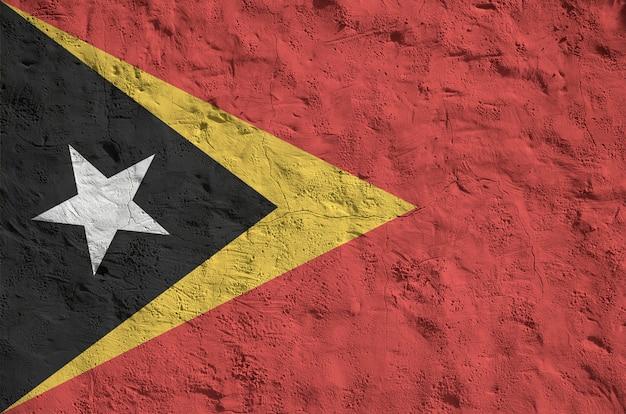 Vlag van oost-timor afgebeeld in heldere verfkleuren op oude reliëf pleistermuur.