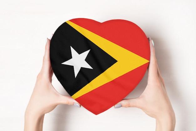 Vlag van oost-timor op een hartvormige doos in een vrouwelijke handen.