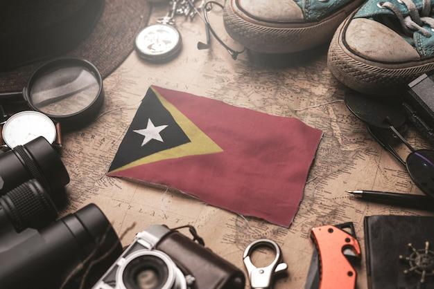 Vlag van oost-timor tussen de accessoires van de reiziger op oude vintage kaart. toeristische bestemming concept.