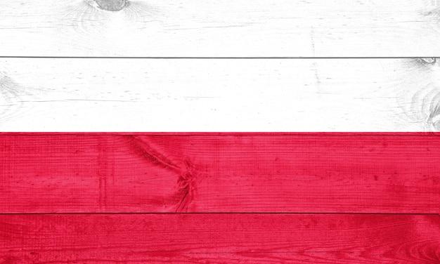 Vlag van polen afgebeeld in heldere verfkleuren op oude houten muur.