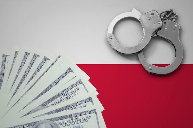 Vlag van polen met handboeien en een bundel dollars. het concept van illegale bankactiviteiten in amerikaanse valuta