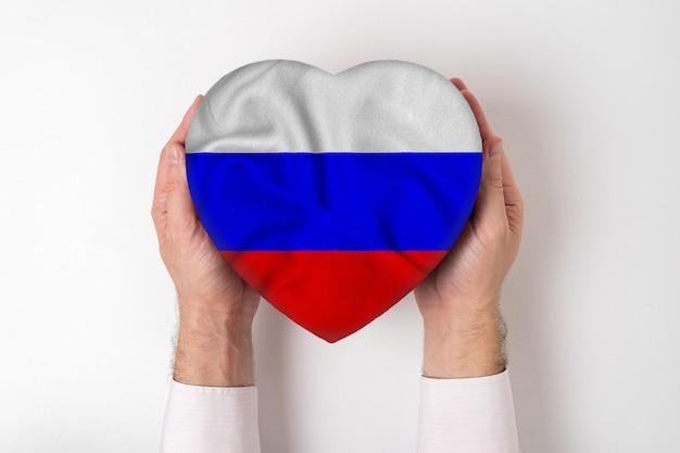 Vlag van rusland op een hartvormige doos in mannelijke handen. witte achtergrond