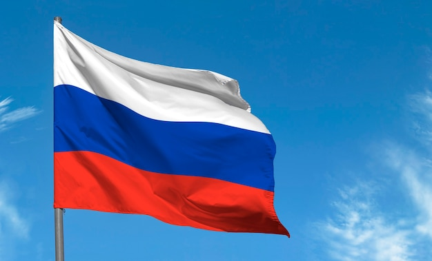Vlag van rusland zwaaien tegen blauwe hemel
