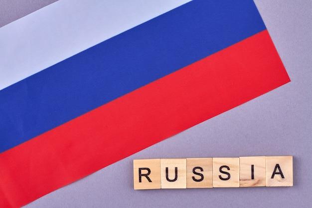 Vlag van russisch geïsoleerd op violette achtergrond. houten blokken maakten naam van land. geïsoleerd op violette achtergrond.