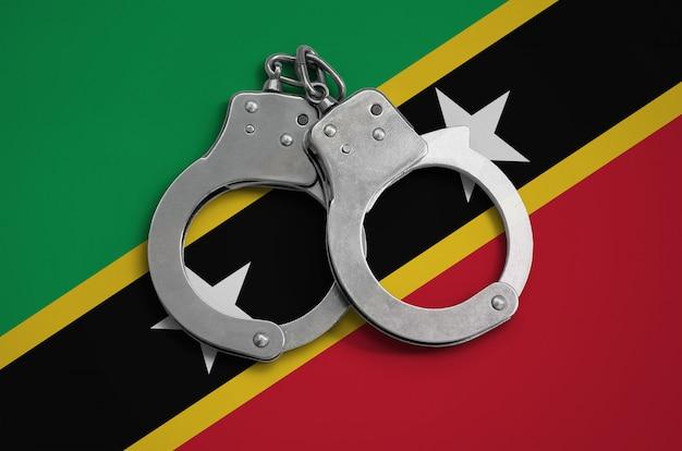 Vlag van saint kitts en nevis en handboeien van de politie. het concept van de naleving van de wet in het land en bescherming tegen criminaliteit