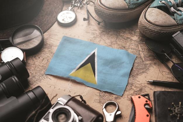 Vlag van saint lucia tussen accessoires van de reiziger op oude vintage kaart. toeristische bestemming concept.