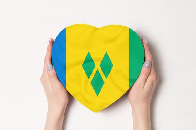 Vlag van saint vincent en de grenadines op een hartvormige doos in een vrouwelijke handen.