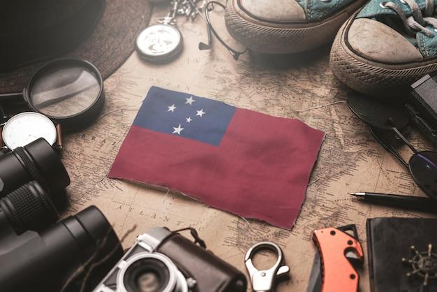Vlag van samoa tussen accessoires van de reiziger op oude vintage kaart. toeristische bestemming concept.