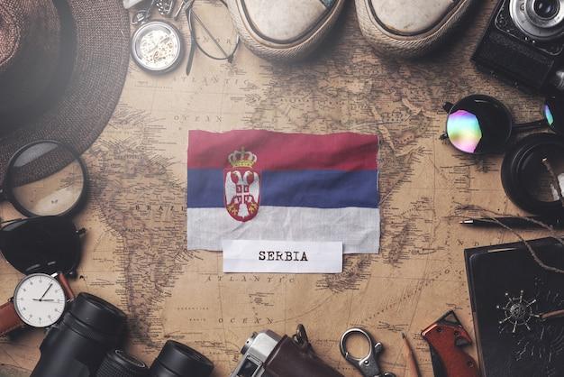 Vlag van servië tussen traveler's accessoires op oude vintage kaart. overhead schot