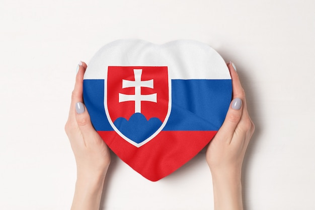 Vlag van slowakije op een hartvormige doos in een vrouwelijke handen op wit
