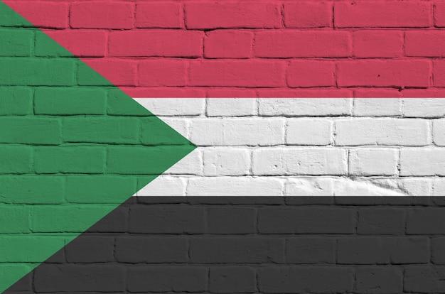 Vlag van soedan afgebeeld in verfkleuren op oude bakstenen muur. geweven banner op de grote achtergrond van het bakstenen muurmetselwerk