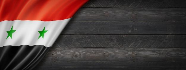 Vlag van syrië op zwarte houten muur. panoramisch.
