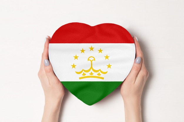 Vlag van tadzjikistan op een hartvormige doos in een vrouwelijke handen.