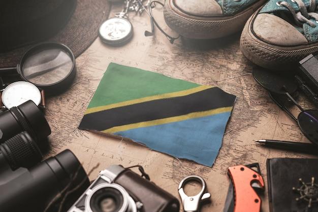 Vlag van tanzania tussen de accessoires van de reiziger op oude vintage kaart. toeristische bestemming concept.