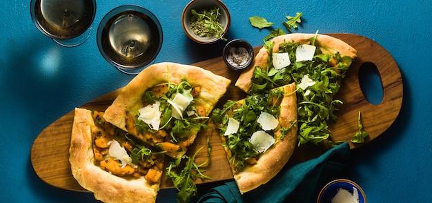 Vlag van traditionele italiaanse witte pizza met taleggio en pecorino kaas, gekarameliseerde pompoen en rucola op de blauwe tafel