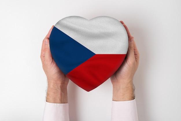 Vlag van tsjechië op een hartvormige doos in mannelijke handen. witte achtergrond