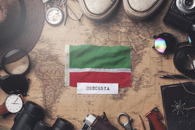 Vlag van tsjetsjeense republiek tussen accessoires van de reiziger op oude vintage kaart. overhead schot