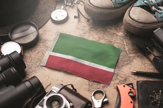 Vlag van tsjetsjeense republiek tussen accessoires van de reiziger op oude vintage kaart. toeristische bestemming concept.