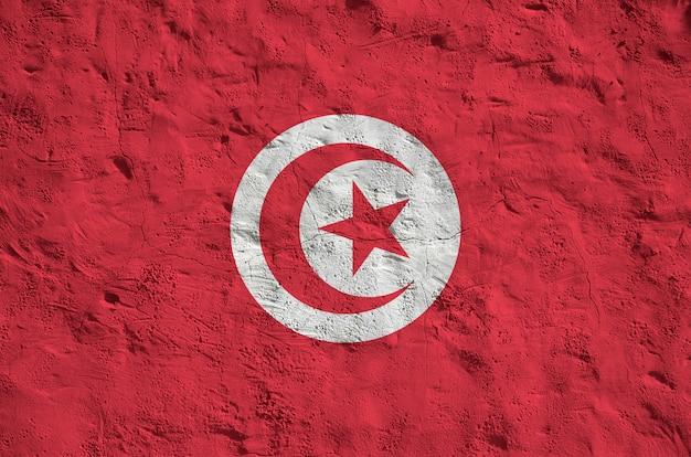 Vlag van tunesië afgebeeld in heldere verfkleuren op oude reliëf pleistermuur.