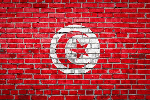 Vlag van tunesië op een bakstenen muur