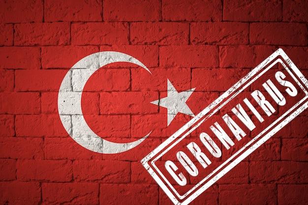 Vlag van turkije met originele verhoudingen. gestempeld met het coronavirus. bakstenen muur textuur. corona-virusconcept. op de rand van een covid-19- of 2019-ncov-pandemie.