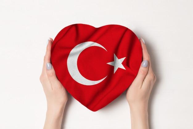 Vlag van turkije op een hartvormige doos in een vrouwelijke handen